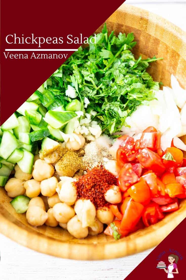 A wooden bowl with chickpeas, cucumbers and Tomato salad.