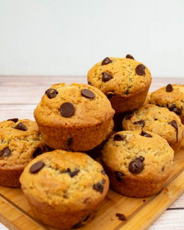 a stack of chocolate chip muffins on a wooden board