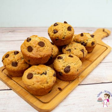 A stack of chocolate chip muffins on a wooden board.