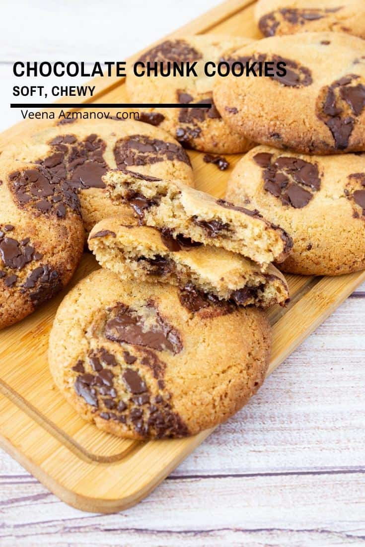 A stack of chocolate chunk cookies on a wooden board.