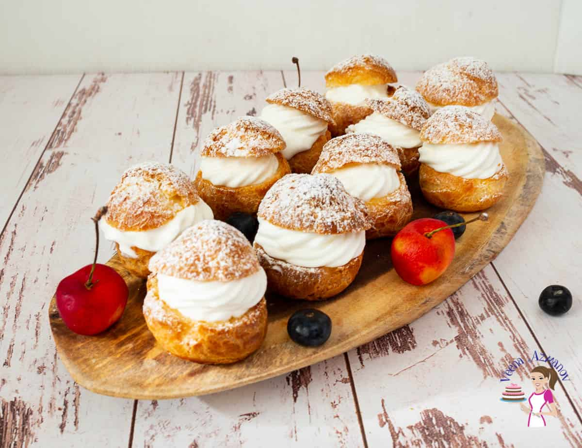 Several cream puffs arranged on a wooden tray.