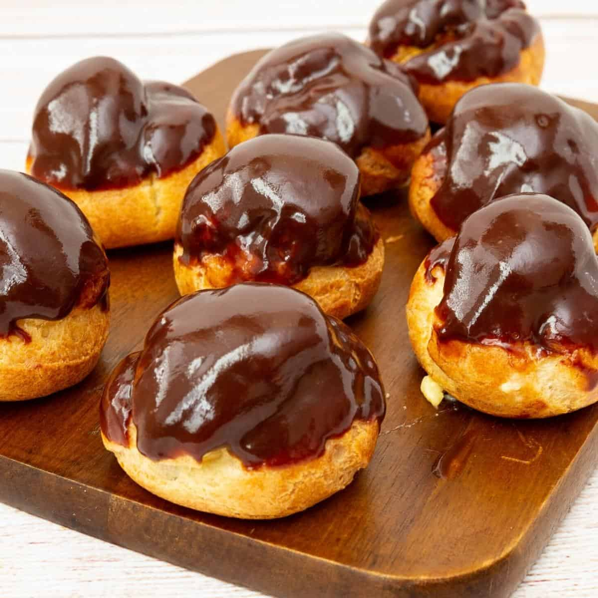 Chocolate glazed profiteroles on a wooden board.