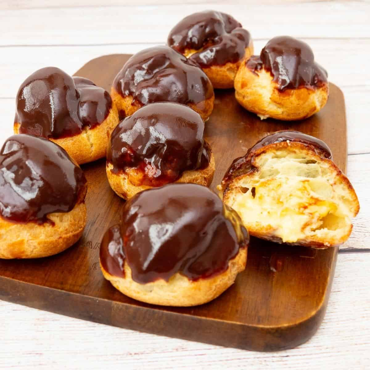 A wooden board with cream puffs stuffed with pastry cream.