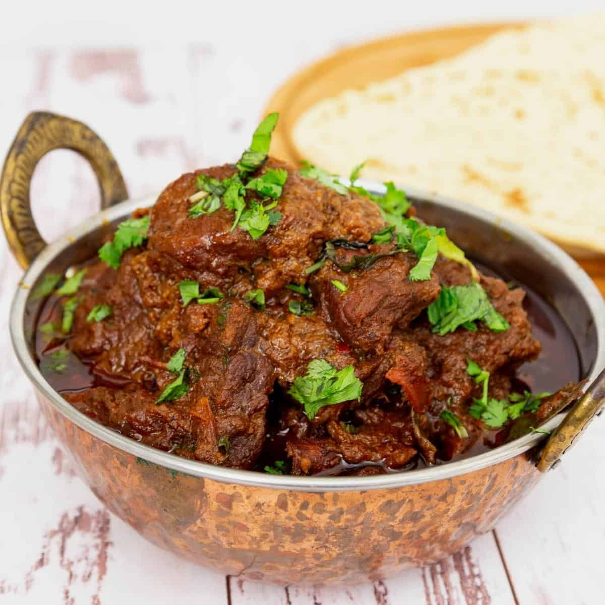 Indian lamb curry in a copper pot.