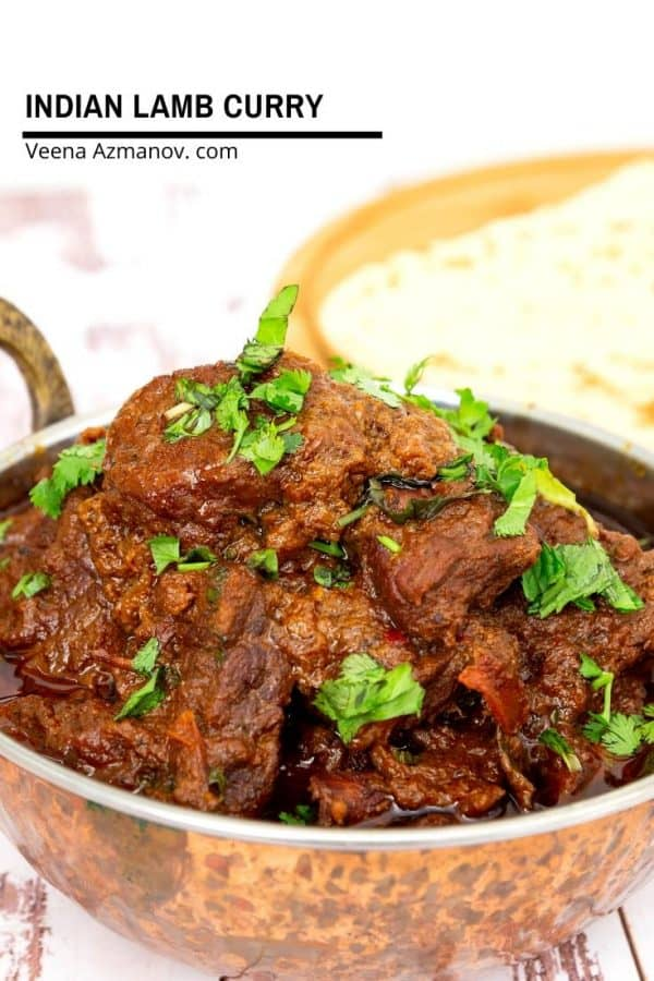 A close up of lamb curry in a metal dish.