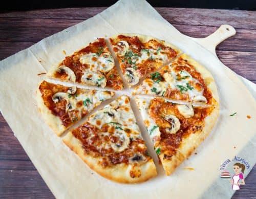 A sliced pizza pie on a table.