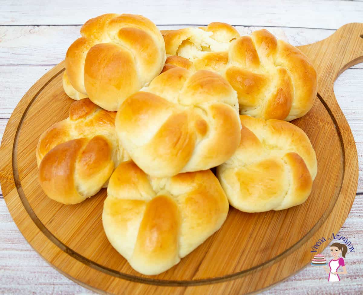 A stack of dinner rolls on a wooden plate.