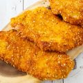 3 Parmesan crusted chicken breasts on a wooden board.