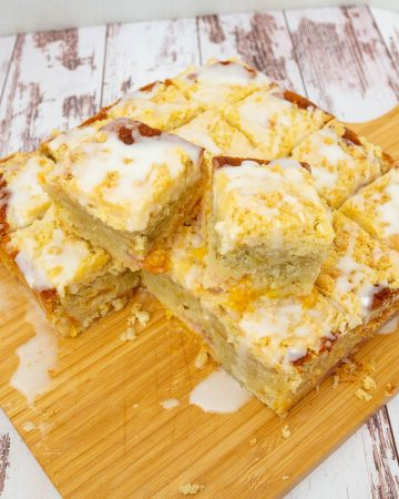 A stack of peach crumble cake squares on a wooden board.