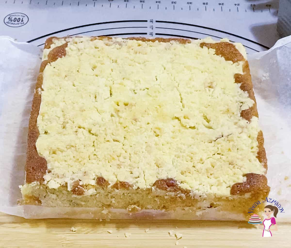 A coffee cake with peaches and crumble on a wooden board.