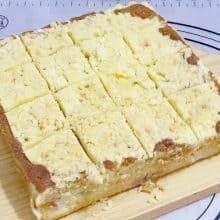 Sliced peach crumble cake on a cake baord.