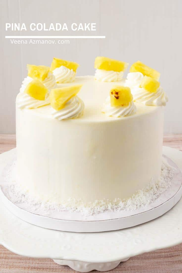 A pineapple and coconut cake on a cake board.