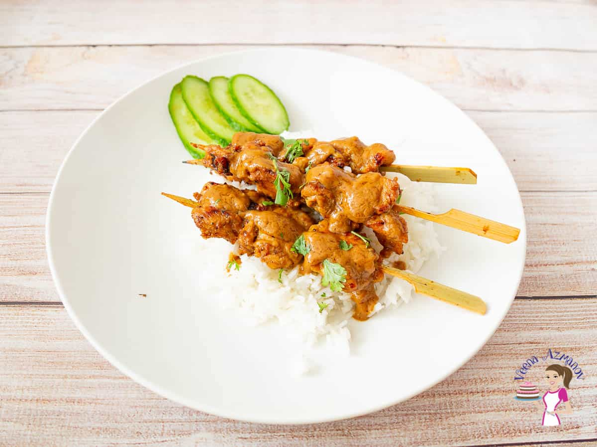 A plate of chicken skewers with sliced cucumbers and rice.