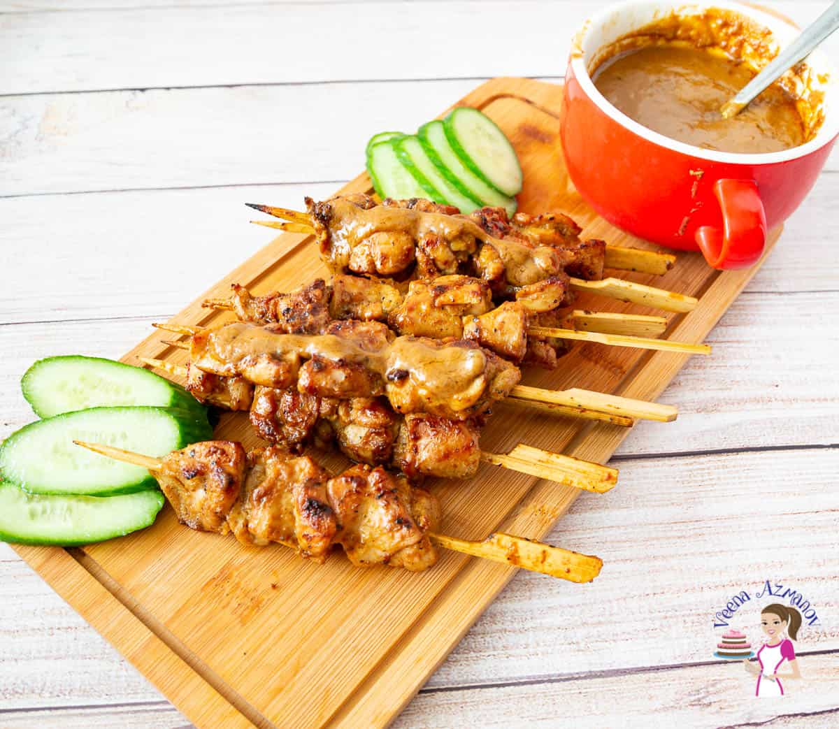 A stack of chicken skewers on a wooden tray with sliced cucumbers and a bowl of peanut sauce.