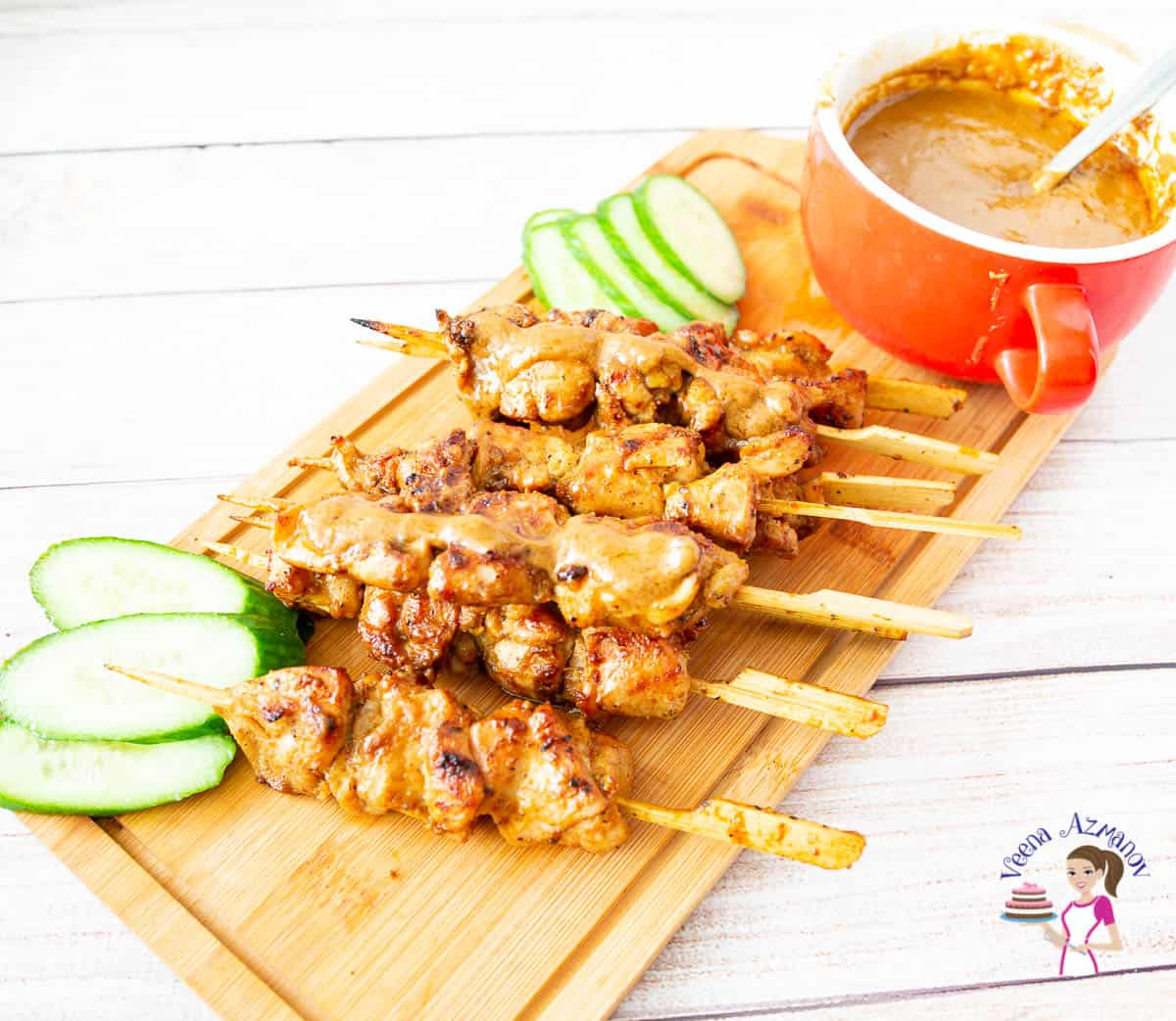 A stack of chicken satay skewers on a wooden tray with sliced cucumbers and a bowl of peanut sauce.