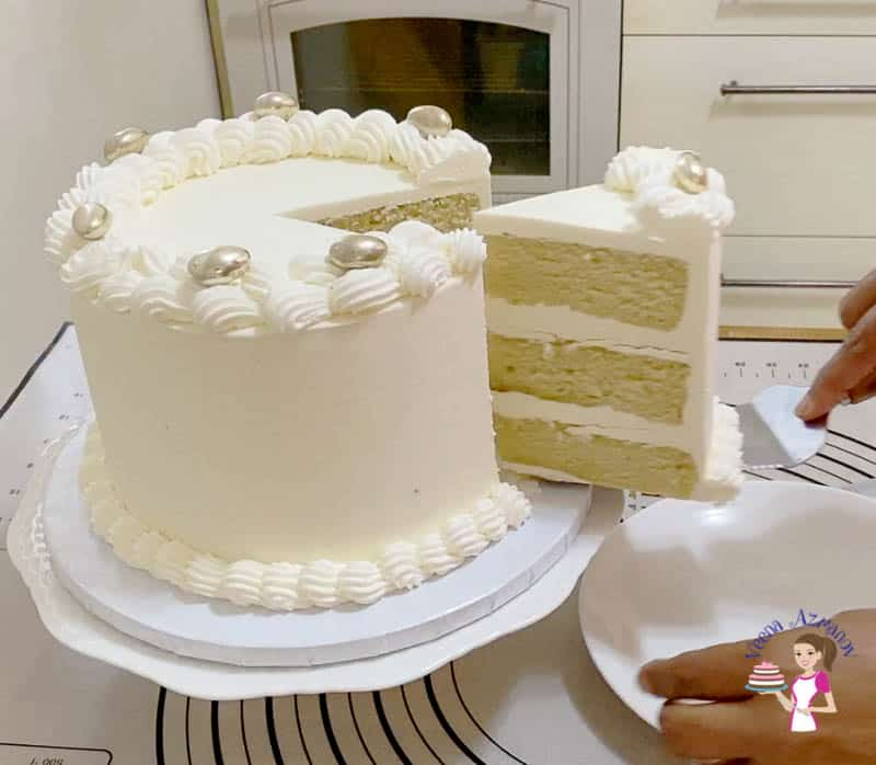 A white layer cake being sliced on a cake stand.