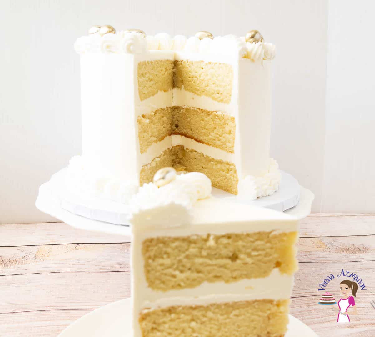 A white wedding cake on a cake stand with a slice of the cake on a plate.