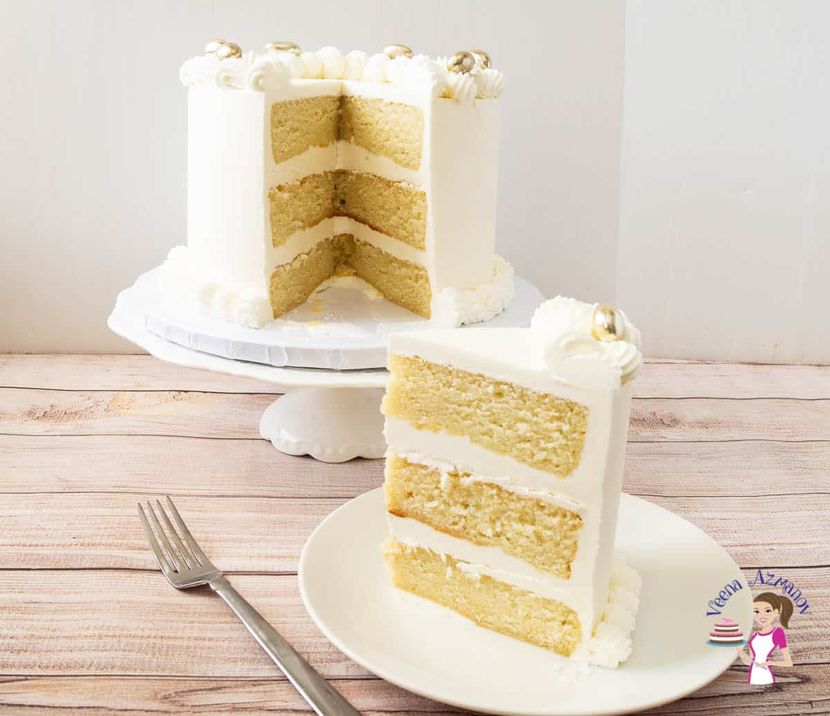 A slice of vanilla layer cake on a plate, with the rest of the cake on a cake stand.