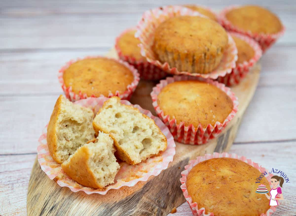 A broken banana muffin and a stack of banana muffins on a wooden tray.