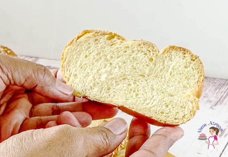 A person holding a slice of challah bread.