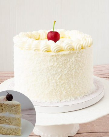 A frosted coconut layer cake on a cake stand.