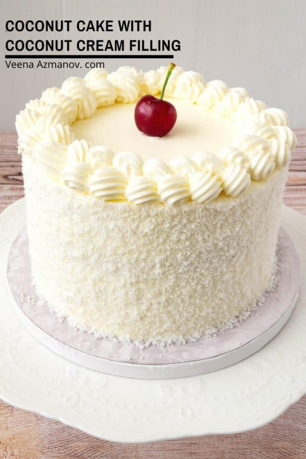 A coconut cake with a cherry on top.