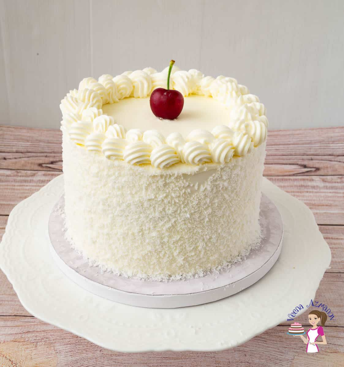 A coconut cake on a cake stand with a cherry on top.