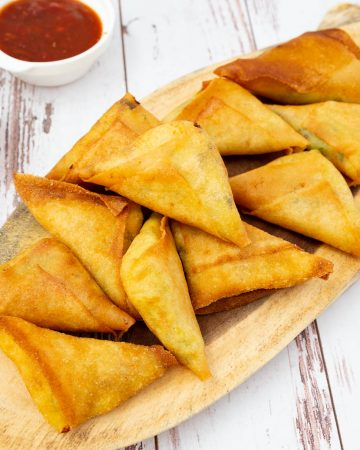 A stack of samosas on a wooden board.