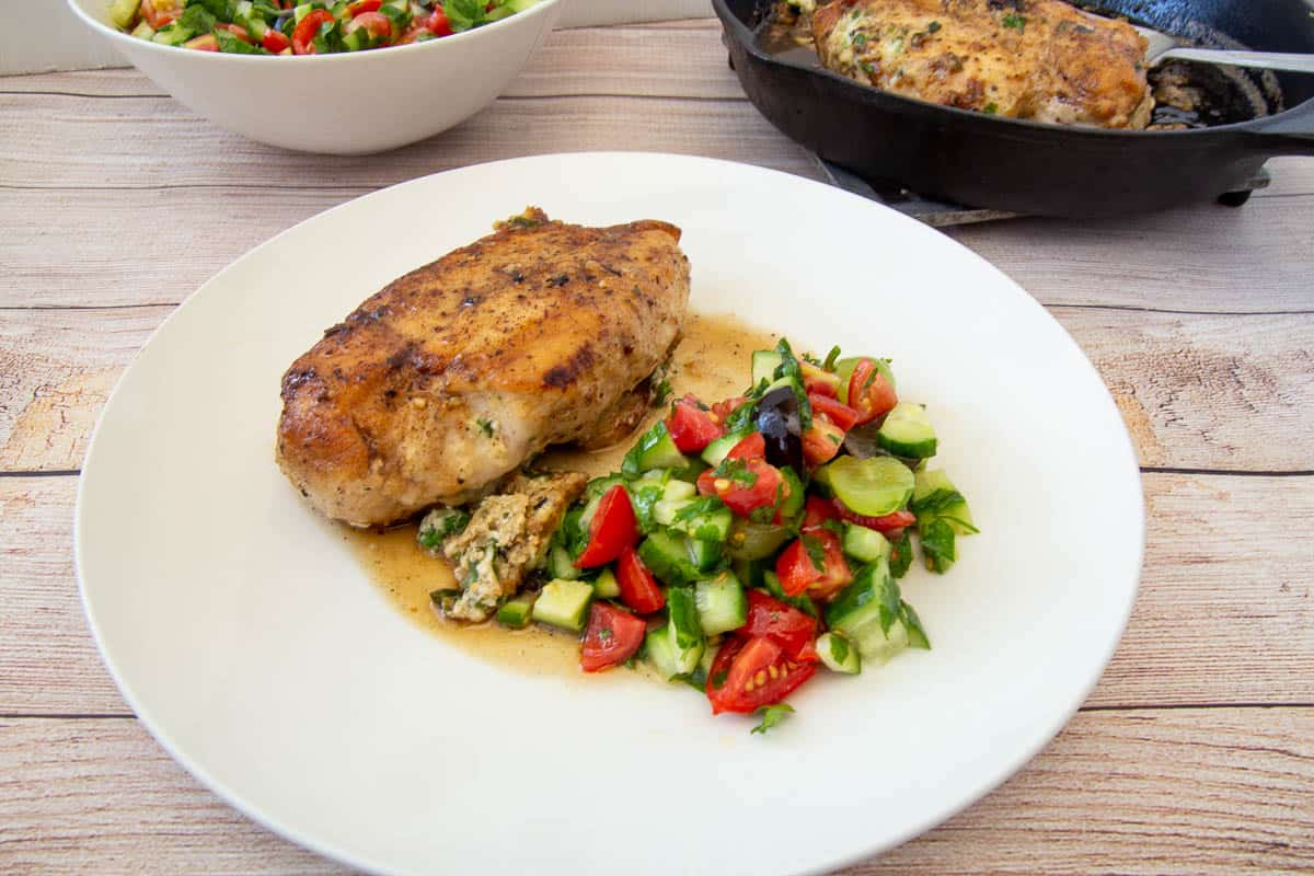 A plate with cheese-stuffed chicken breast and tomatoes and cucumbers salad.