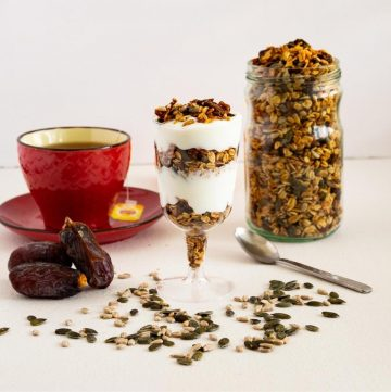 Granola in a jar next to a glass with yogurt parfait.