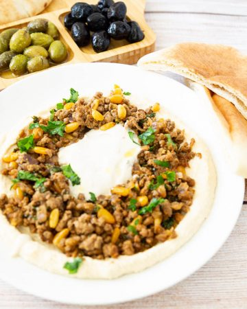 A plate of hummus and ground beef.
