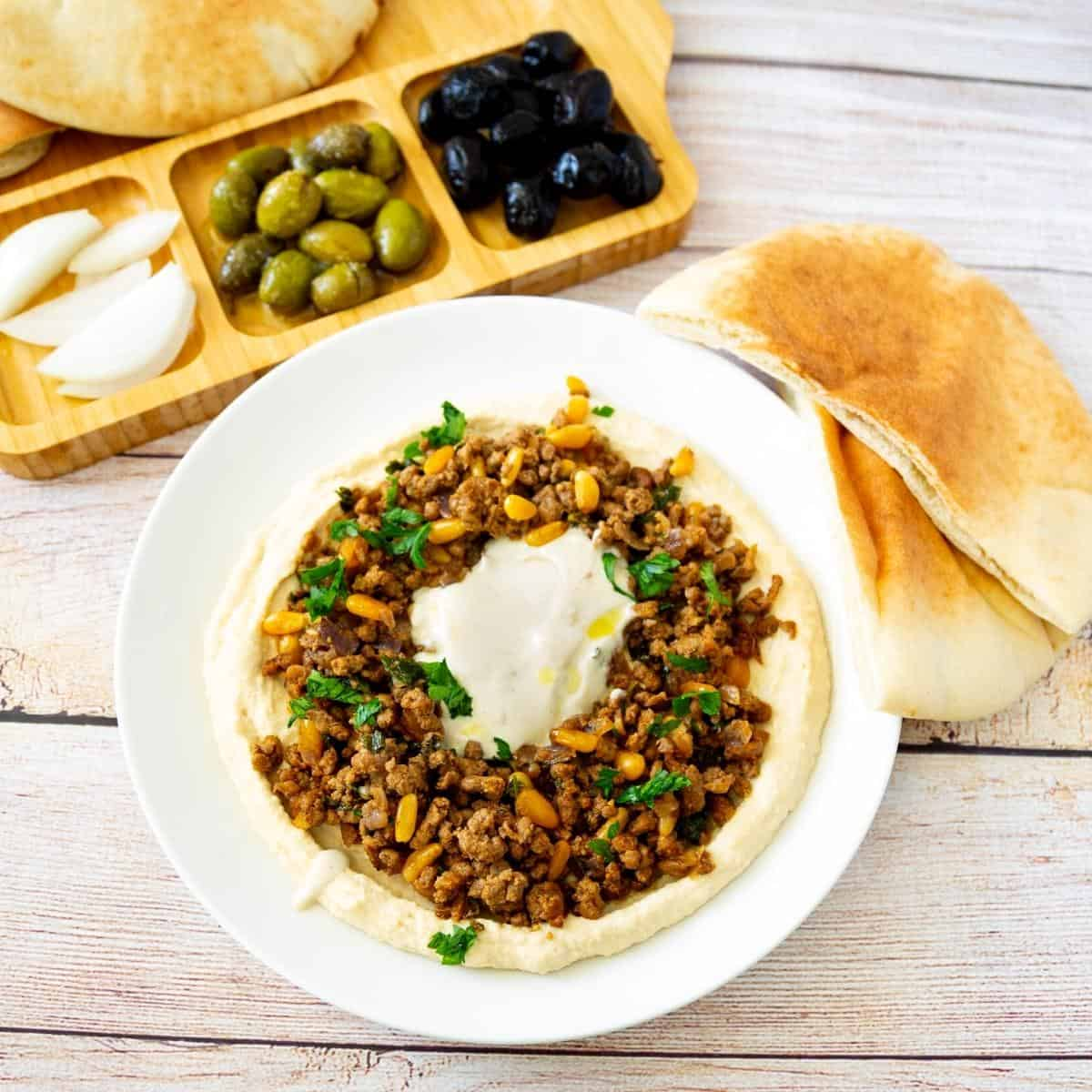 A plate with ground beef and hummus.
