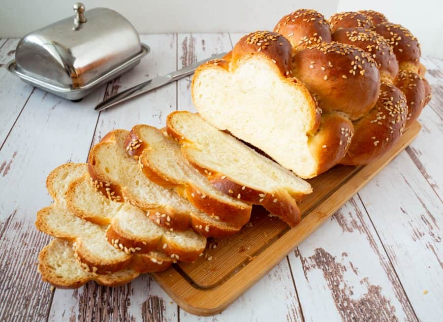 Sliced challah bread on a wooden board.