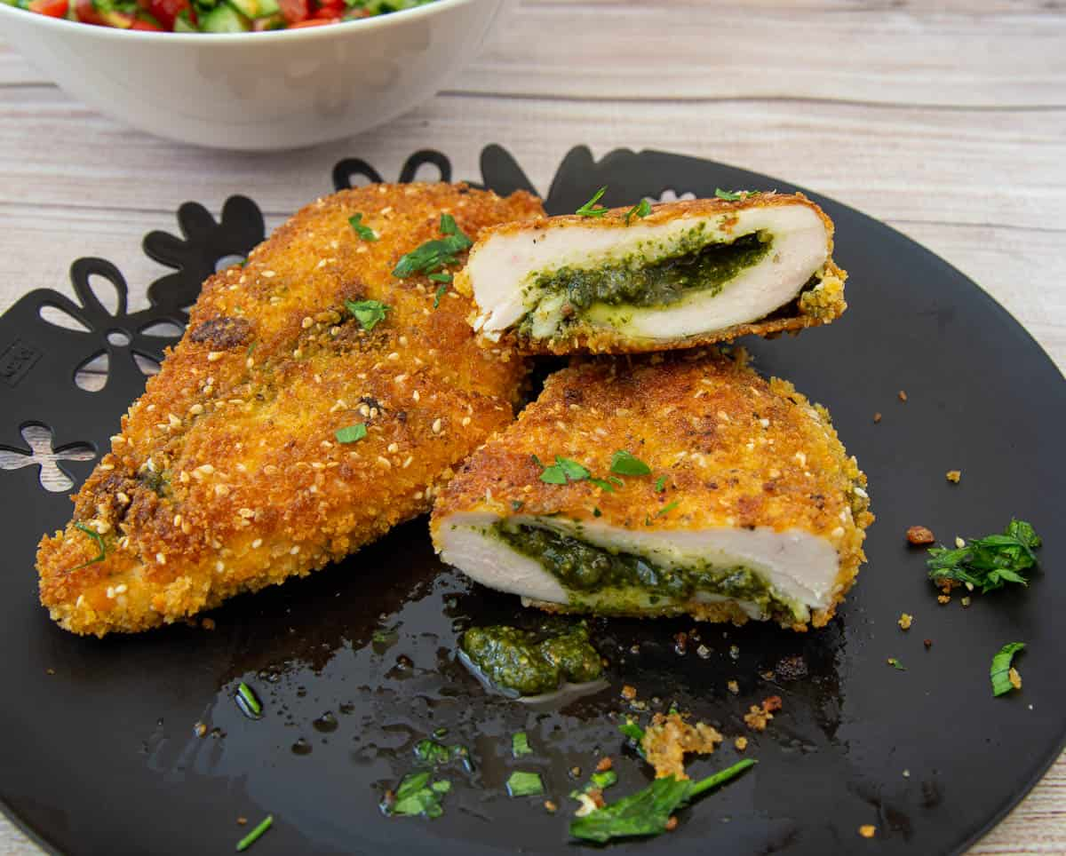 A plate with two pesto-stuffed chicken breasts, one whole and one cut in half.