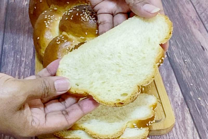 A person holding a slice of a challah bread.