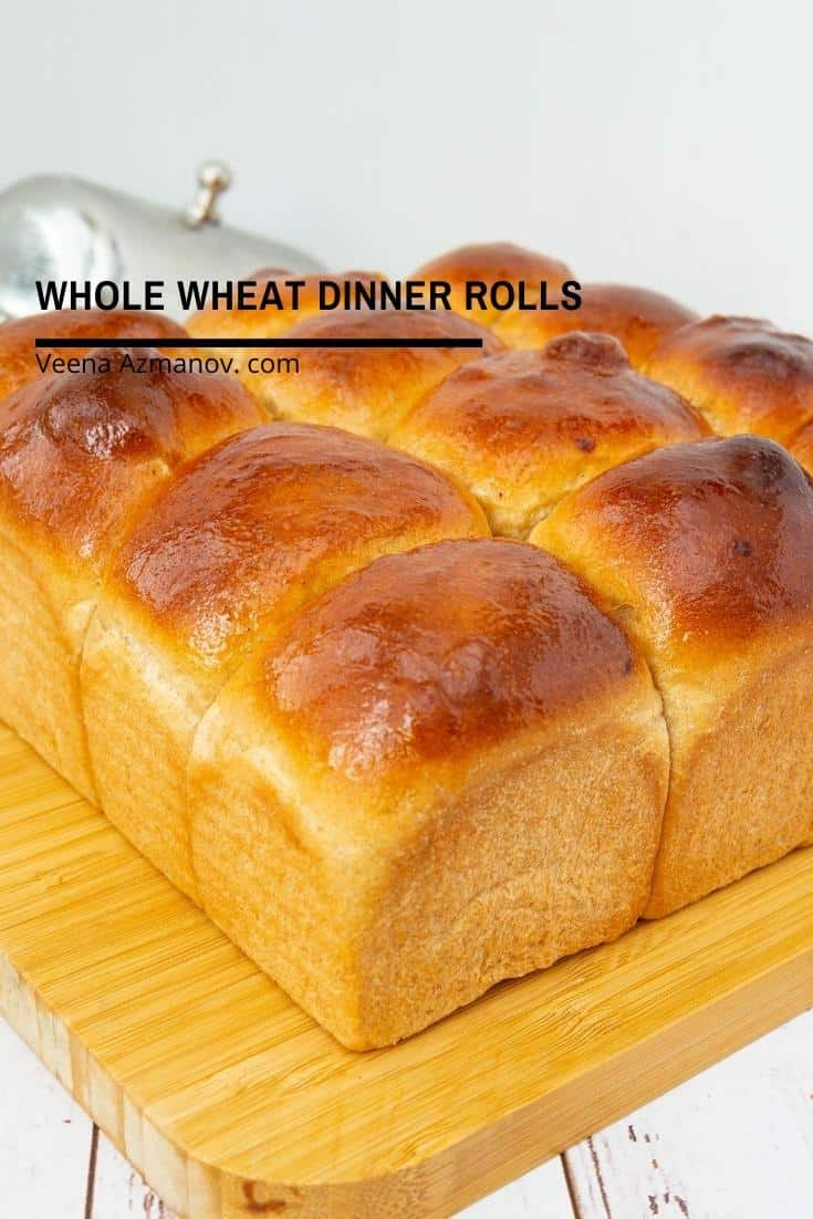 Whole wheat dinner rolls on a wooden board.
