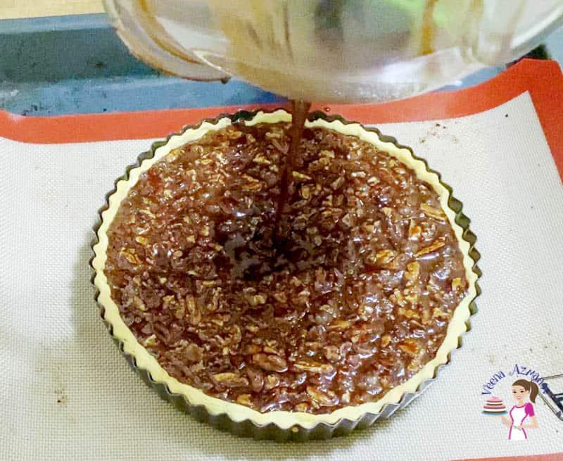 Pour chocolate pecan pie filling in the pie crust