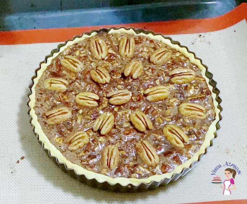 Top the chocolate pecan pie filling will pecan halves.