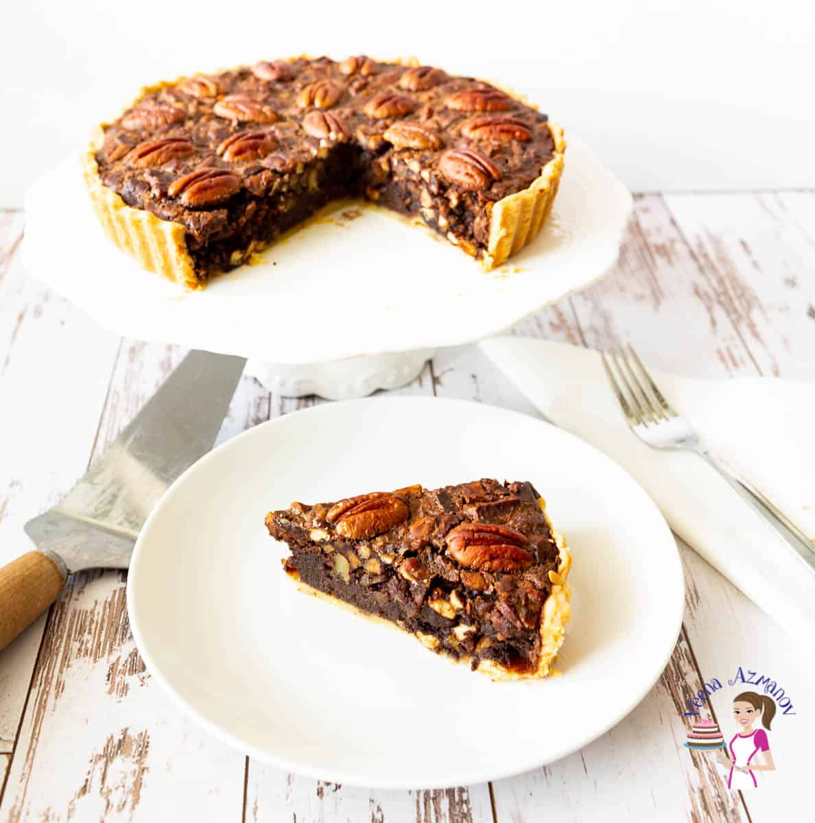 A slice of pecan pie on a plate, with the remaining pie on a cake stand.