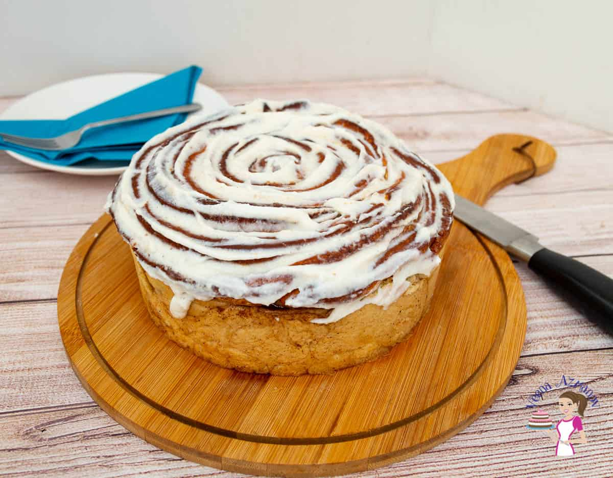 A giant cinnamon roll on a wooden board.