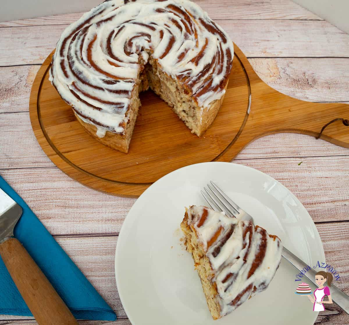 A giant cinnamon roll on a wooden board and a slice of it on a plate.