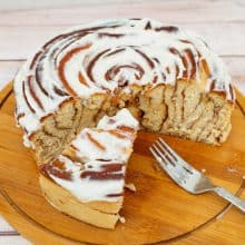 A large giant size cinnamon roll on a wooden board.