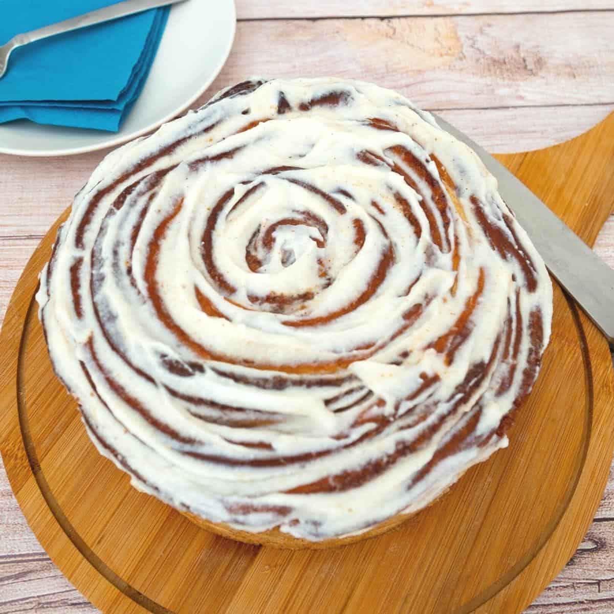 A large cinnamon roll on a wooden board.