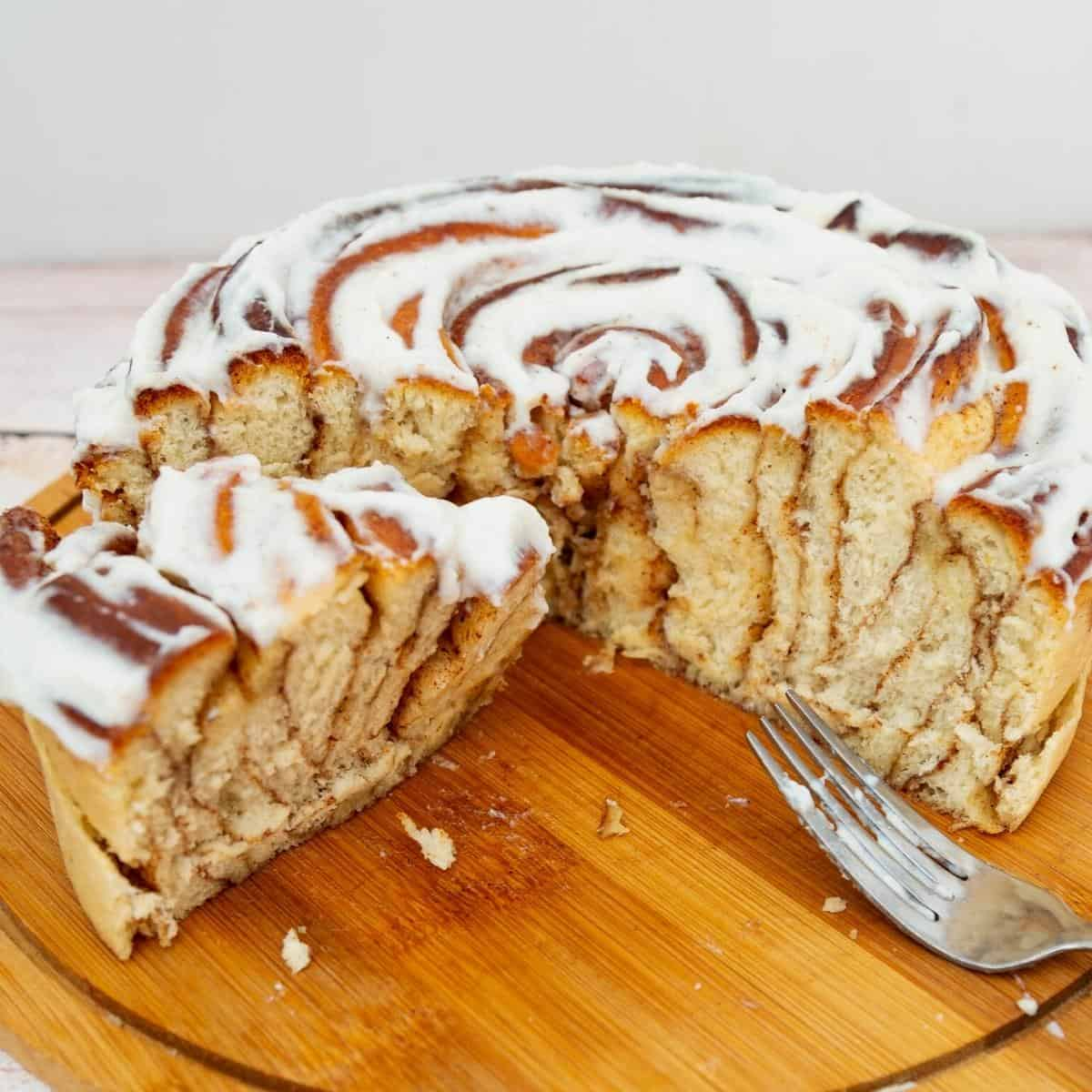 A sliced giant cinnamon roll on the wooden board.