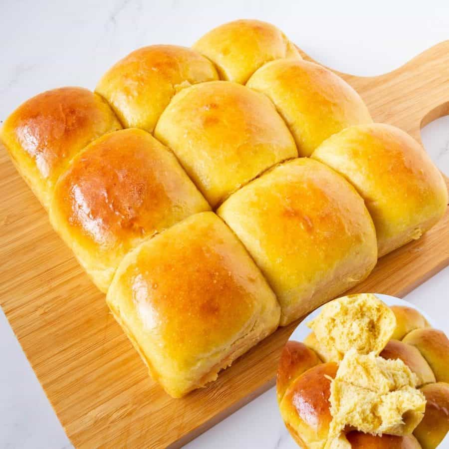 Soft dinner rolls on a wooden board.