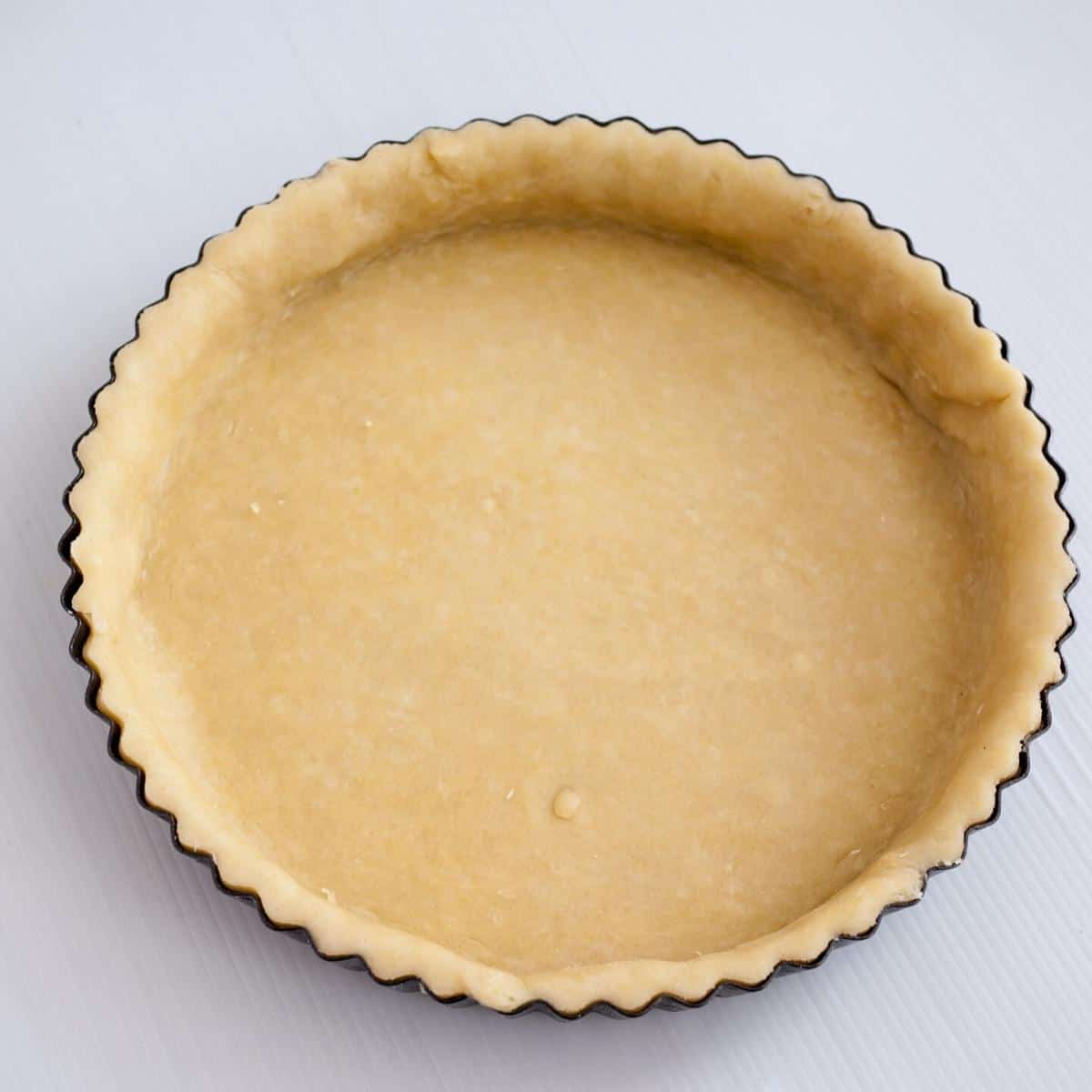 A pre-baked quiche crust in a quiche pan.