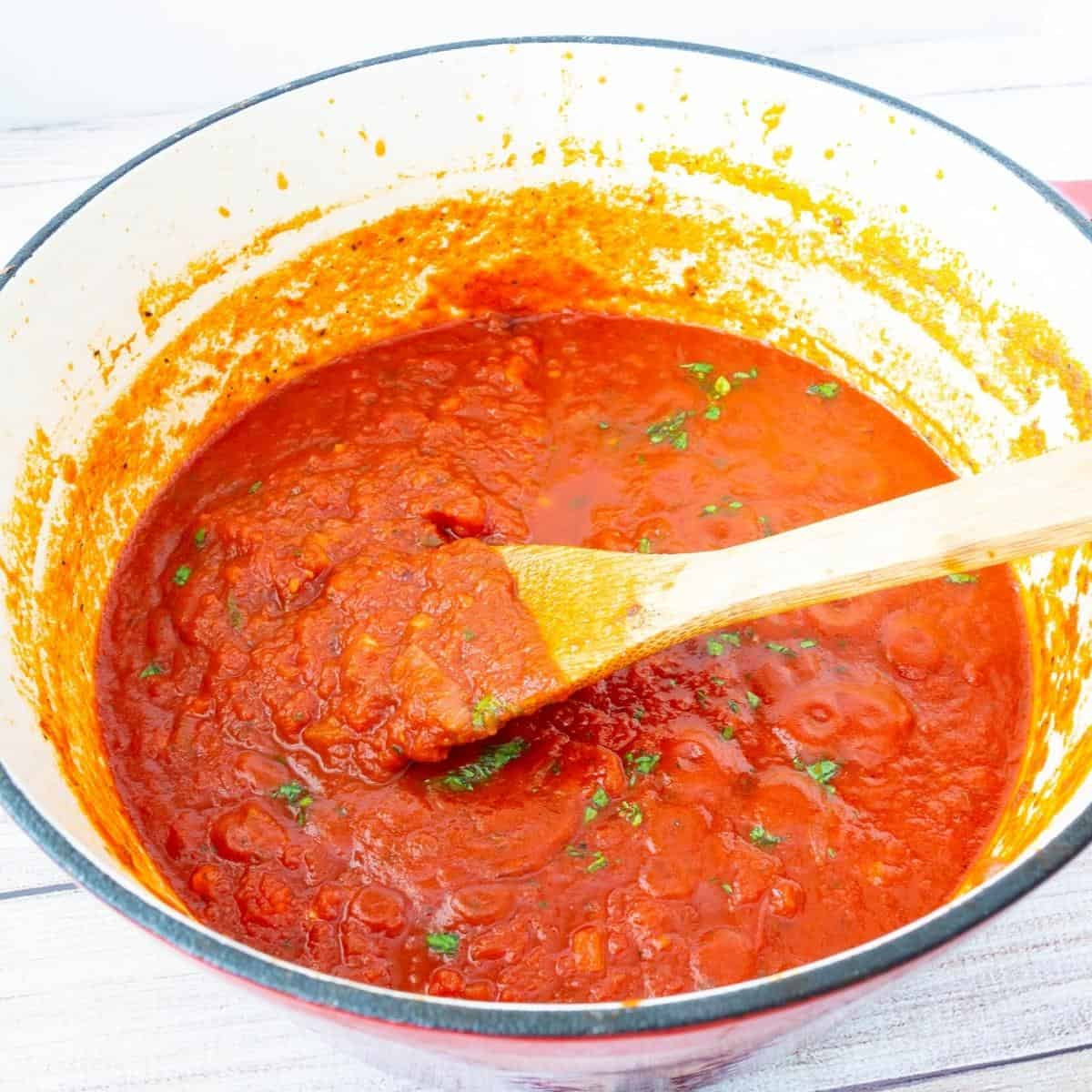 A Dutch oven with tomato sauce.