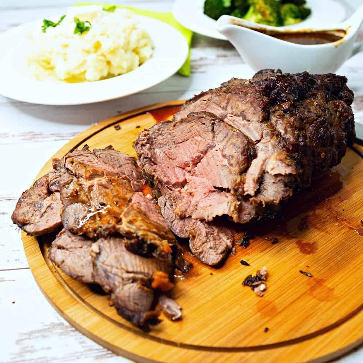 A sliced roast beef on a wooden board.