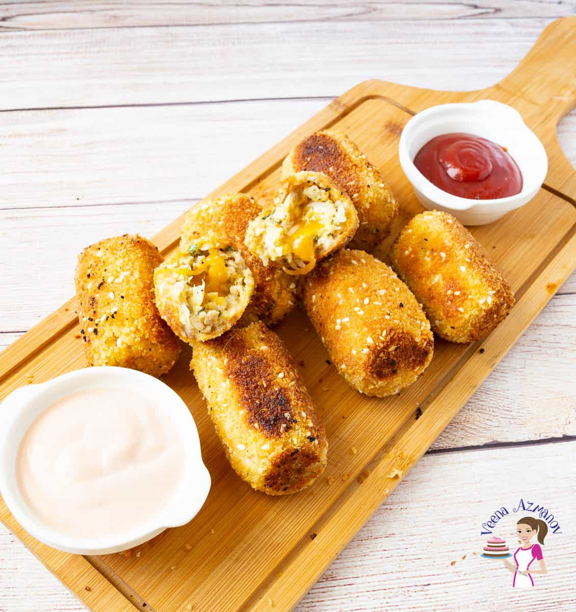 Chicken croquettes with dipping sauces on a wooden board.