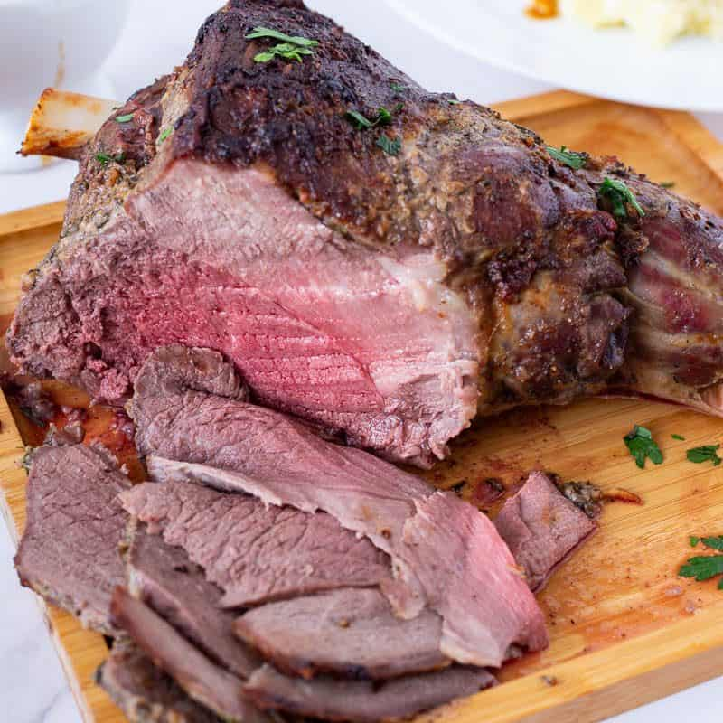 A sliced leg of lamb on a wooden board